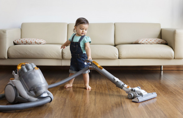 Young boy wearing denim dungarees, standing in front of sofa, hoovering hardwood floor.